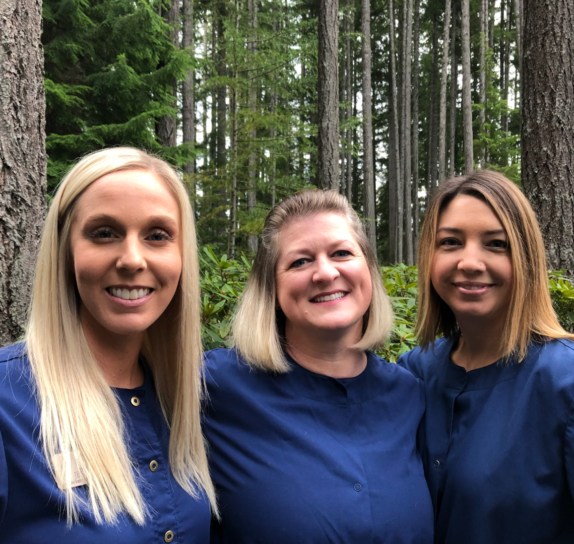 A few CLD Employees smiling in the forest